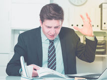 Businessman in suit worrying at the computer Stock Photography