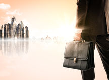 Businessman with suitcase against modern city Stock Images