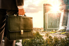 Businessman with suitcase against modern city Stock Photography