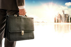 Businessman with suitcase against modern city Royalty Free Stock Images