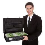 Businessman with suitcase full of cash Stock Photo