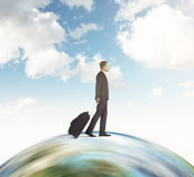 Businessman with suitcase going on the globe with sky Stock Photos