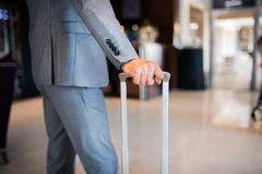Businessman with suitcase in a hotel entrance hall. Unrecognizable businessman with suitcase in a hotel entrance hall Stock Photo