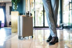 Businessman with suitcase in a hotel entrance hall. Unrecognizable businessman with suitcase in a hotel entrance hall Stock Photography