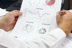 Businessman Summary report and capital market plan analyzing ord. Er plan, pen and calculator on paperwork Stock Image