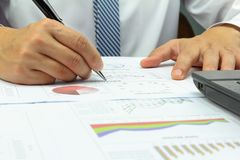 Businessman Summary report  capital market plan finance. With calculate about cost at table office office Stock Photo