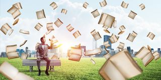 Businessman in summer park announcing something in loudspeaker and books falling from above. Young businessman sitting on bench and screaming emotionally in Royalty Free Stock Photos