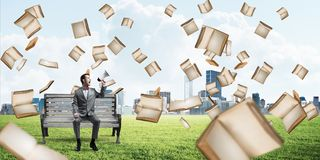 Businessman in summer park announcing something in loudspeaker and books falling from above. Young businessman sitting on bench and screaming emotionally in stock photo
