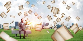 Businessman in summer park announcing something in loudspeaker and books falling from above. Young businessman sitting on bench and screaming emotionally in royalty free stock photography