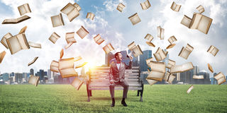 Businessman in summer park announcing something in loudspeaker and books falling from above. Young businessman sitting on bench and screaming emotionally in stock photos