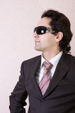 The businessman in sunglasses. Portrait of the businessman in a brown suit in sunglasses royalty free stock image