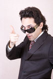 The businessman in sunglasses. Portrait of the businessman in a brown suit in sunglasses royalty free stock photo
