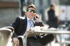 Businessman in sunglasses having breakfast coffee early morning reading newspaper news talking on mobile phone Royalty Free Stock Image