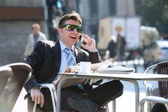 Businessman in sunglasses having breakfast coffee early morning reading newspaper news talking on mobile phone Stock Photography