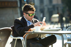 Businessman in sunglasses having breakfast coffee reading newspaper using internet on mobile phone Stock Photography