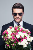 Businessman in sunglasses holding flowers Royalty Free Stock Image