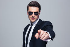 Businessman in sunglasses pointing at camera Royalty Free Stock Photography