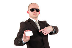 Businessman with sunglasses pointing at a card Royalty Free Stock Images