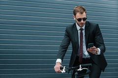 Businessman in sunglasses using smartphone while riding bicycle Royalty Free Stock Photo