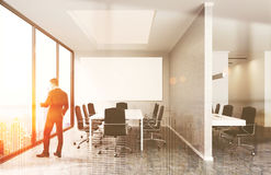 Businessman in sunlit office. Young businessman standing near office window looking at New York. Large white table surrounded by armchairs. Big whiteboard on Stock Images