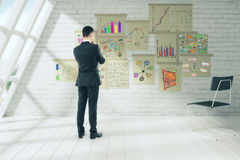 Businessman in a sunny office looking at financial charts on the. Wall, close up stock photography