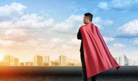A businessman in super hero cape standing turned back on the sky background with cityscape below. royalty free stock images
