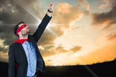 Businessman in super hero costume with hand raised against sky. Digital composite of Businessman in super hero costume with hand raised against sky royalty free stock photo