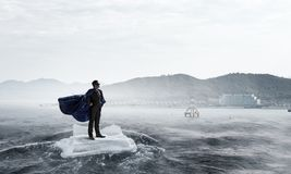 Surfing sea on ice floe. Mixed media. Businessman super hero on ice block floating in sea . Mixed media Royalty Free Stock Photo