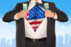 Businessman superhero clutching money and opening shirt to reveal United States of America flag. Businessman superhero clutching money and opening shirt to stock images