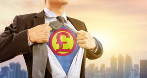 Businessman in superhero costume with British pound sterling sign. And city background stock photography