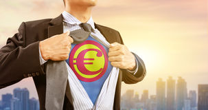 Businessman in superhero costume with Euro currency and city background Royalty Free Stock Photography