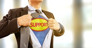 Businessman in superhero costume in help and support royalty free stock photography