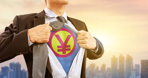 Businessman in superhero costume with Japanese Yen sign. Japanese money currency and city background Stock Images
