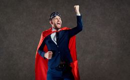 A businessman in a superhero costume is a winner. stock images