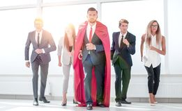 Businessman superhero and his business team are stepping togethe stock photography