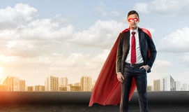 A businessman in superhero mask and cape on the sky background with many apartment blocks in the distance. Business hero. Development of the community stock image