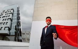 A businessman superhero points finger on a business building bac Stock Photo