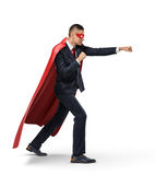 A businessman in a superhero red cape and a mask standing in side view in punch position on white background. Royalty Free Stock Photos