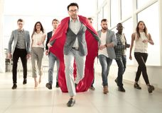 Businessman in a superhero`s cloak is ahead of the business team stock photo