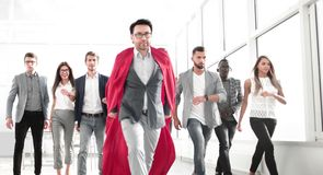 Businessman in a superhero`s cloak is ahead of the business team royalty free stock image