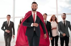 Businessman is a superhero, stepping ahead of his business team royalty free stock photography