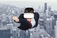 Businessman superhero wearing virtual reality glasses. Flying above a city stock photo