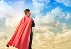 A businessman in superman cape standing turned back on the sky background. Business hero. Confidence and success. New opportunities royalty free stock photos