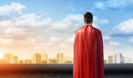 A businessman in superman cape standing turned back on the sky background with cityscape below. Royalty Free Stock Photos