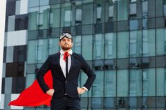 Businessman in a superman costume. Businessman in a superman costume against a business building background Stock Images