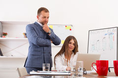 Businessman supervising his female assistant's work on laptop co royalty free stock photo