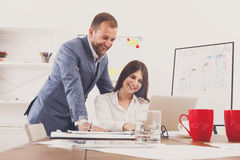 Businessman supervising his female assistant's work on laptop Stock Photo
