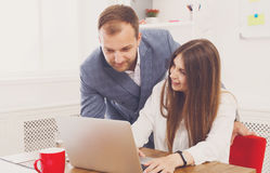 Businessman supervising his female assistant's work on laptop Stock Photos