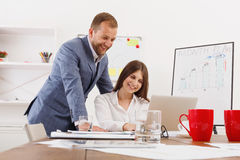 Businessman supervising his female assistant`s work on laptop Royalty Free Stock Images