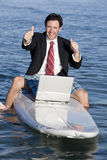 Businessman on Surfboard Royalty Free Stock Image